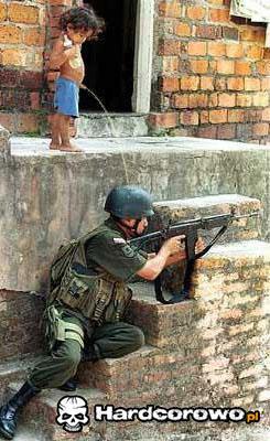 Mały chłopiec daje pić żołnierzowi - 1